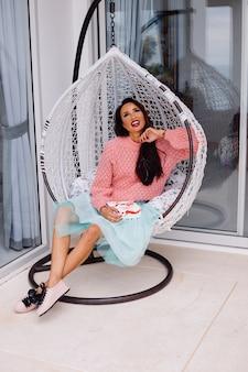 분홍색 스웨터와 파란색 치마 여자는 사탕 상자를 들고 계란 의자에 의해 서