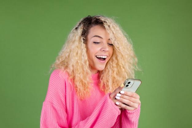 휴대 전화를 들고 녹색에 분홍색 스웨터를 입은 여자 행복 미소 쾌활한 흥분