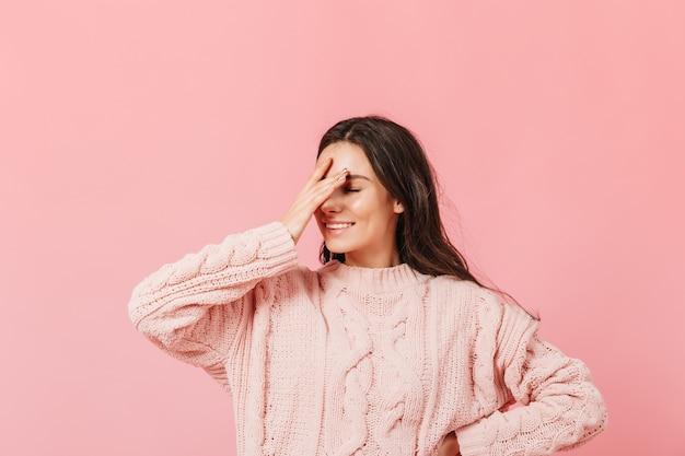 격리 된 배경에 포즈 분홍색 스웨터에 여자입니다. 미소와 함께 재미있는 여자는 안면을 만든다.