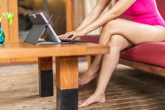 Женщина в розовом купальном костюме работает с ноутбуком в отпуске.