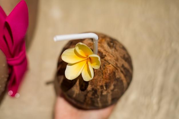 ココナッツのドリンクを飲みながらプールで日焼けピンクの水着の女性