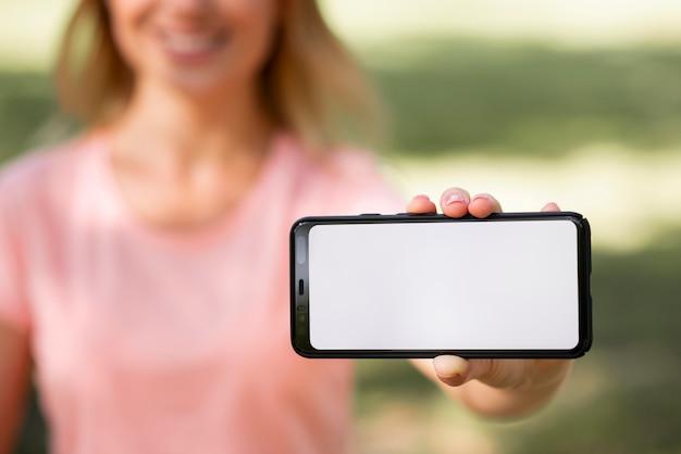 Женщина в розовой футболке и копией пространства горизонтальный мобильный телефон
