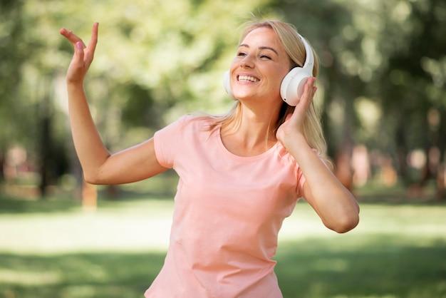 Женщина в розовой футболке слушает музыку