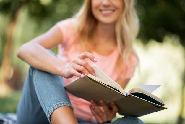 Женщина в розовой футболке читает на открытом воздухе