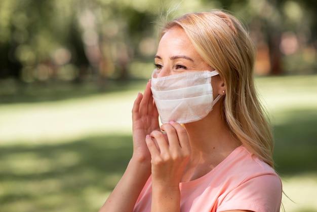 Женщина в розовой футболке в медицинской маске в парке