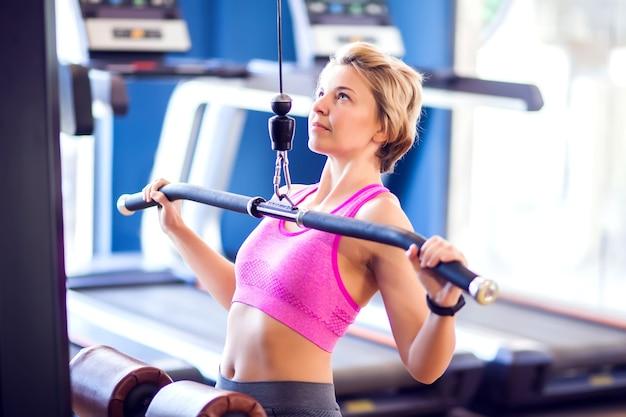 ピンクのトップと短いブロンドの髪の女性がジムで背中の筋肉をトレーニングしています。人、フィットネス、ヘルスケアの概念