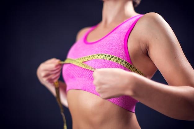 黄色のメーターで胸を測定するピンクのトップの女性。フィットネス、ライフスタイル、健康の概念