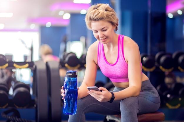 ジムで休んでいる短いブロンドの髪のピンクのトップの女性、水のボトルとスマートフォンでベンチに座っています。人、フィットネス、ヘルスケアの概念