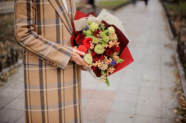 路地の花の花束と格子縞のコートの女性