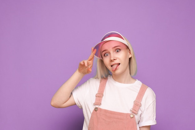 예쁜 캐주얼 드레스에 여자, 분홍색 모자를 쓰고 재미있는 얼굴 만들기