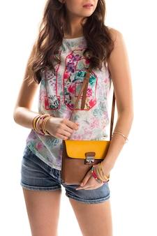 인쇄된 탱크 탑을 입은 여성. 민소매 꽃무늬 상의와 반바지. 젊은 모델은 세련된 핸드백을 들고 있습니다. 편안한 여름옷.