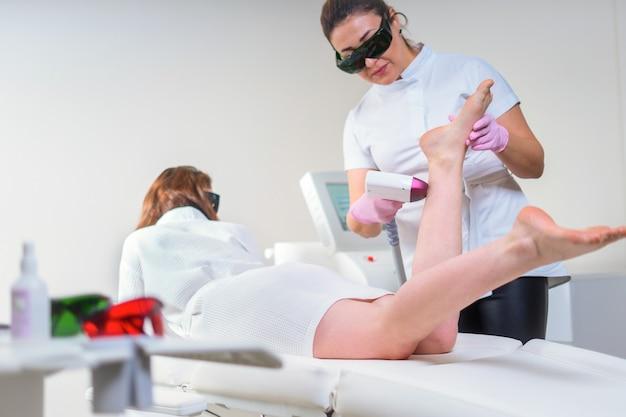 Женщина в профессиональной клинике красоты во время лазерной эпиляции. лечение эпиляции. концепция гладкой кожи