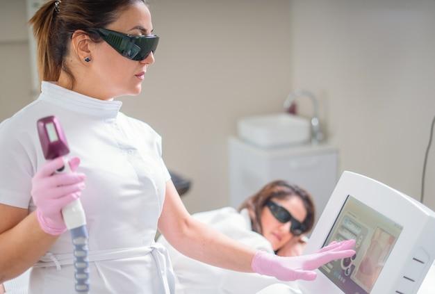 Женщина в профессиональной клинике красоты во время лазерной эпиляции. лечение эпиляции. гладкая кожа