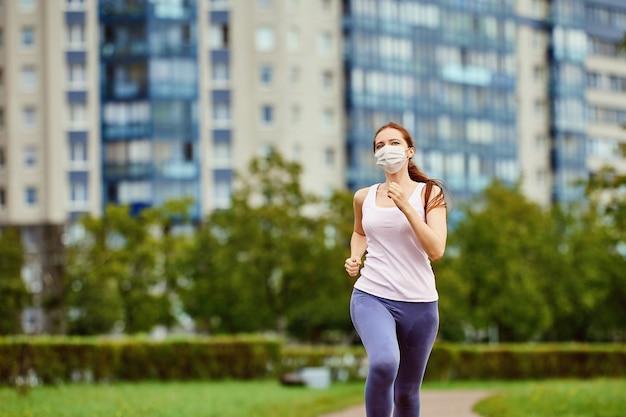 保護フェイシャルマスクの女性は屋外で実行されます