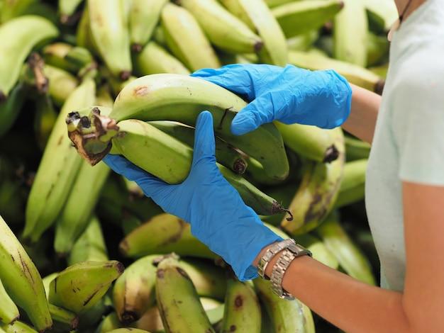 Женщина в защитных перчатках покупает зеленый канарский банан платано в супермаркете во время эпидемии коронавируса.