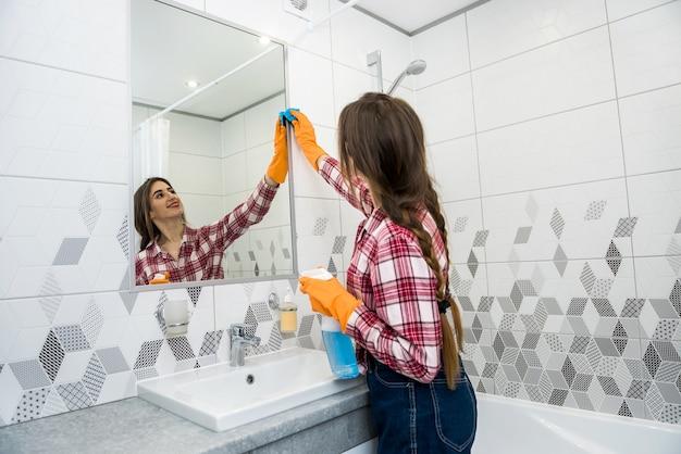 그녀의 집을 청소하는 동안 스프레이와 걸레를 들고 보호 장갑에 여자.