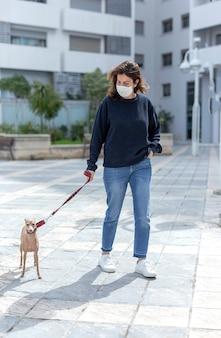 Женщина в защитной маске от коронавируса во время карантина выгуливает собаку
