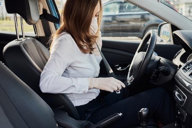 シートベルトを締める保護マスクと手袋の女性
