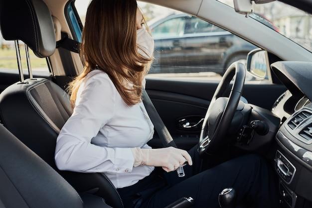 保護マスクと手袋を着用した女性が車のシートベルトを締める