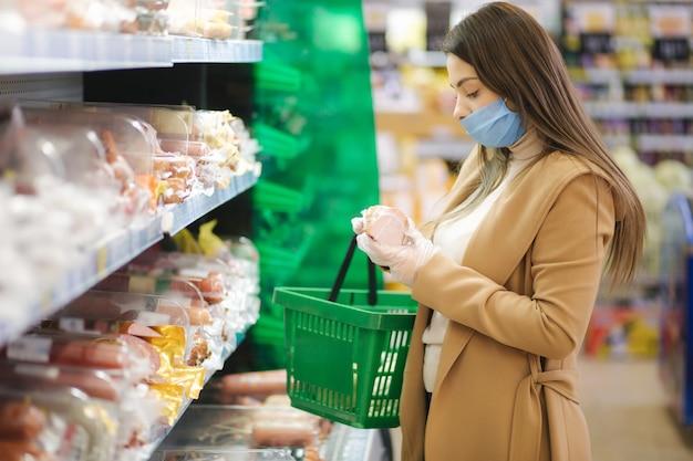 スーパーマーケットに立っている間商品の価格でラベルを読んで保護マスクと手袋の女性