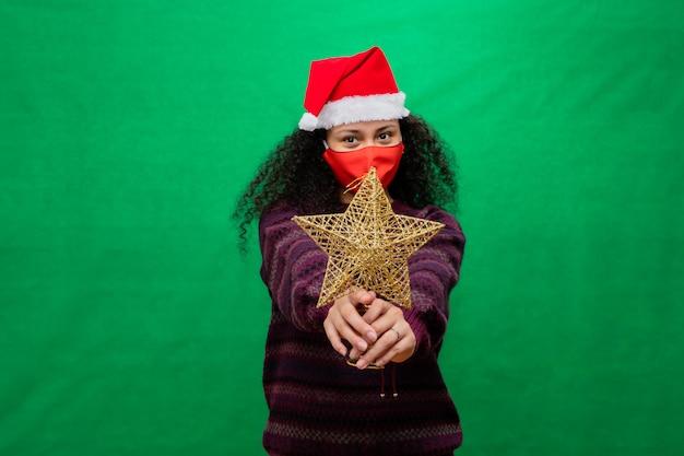 保護マスクとサンタの帽子の女性は両手で黄金のクリスマスの星を保持します