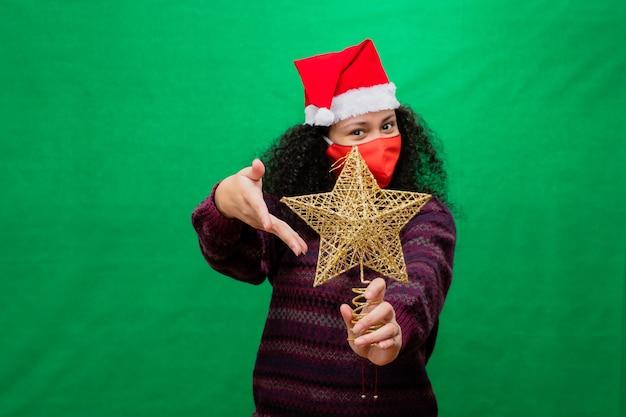 保護マスクとサンタの帽子の女性は両手で黄金のクリスマスの星を提示します