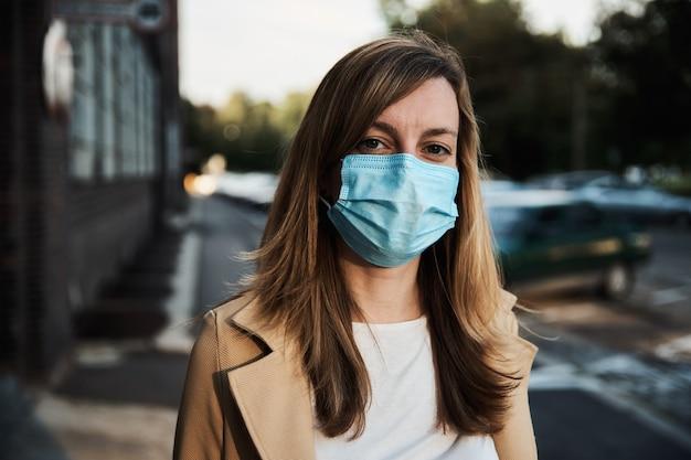 Женщина в защитной маске на городской улице