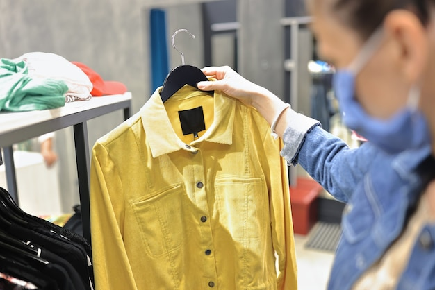 Женщина в защитной маске выбирает одежду в магазине