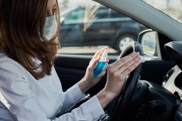 Женщина в защитной маске дезинфицирует автомобиль дезинфицирующим средством