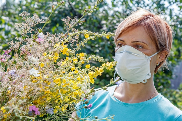 野花の花束を保持し、花粉に対するアレルギーと戦おうとしている保護マスクの女性。自然な背景。アレルギーの概念。