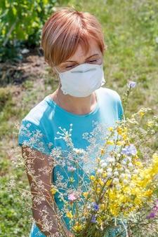 野花の花束を保持し、花粉に対するアレルギーと戦おうとしている保護マスクの女性。自然光。アレルギーの概念。