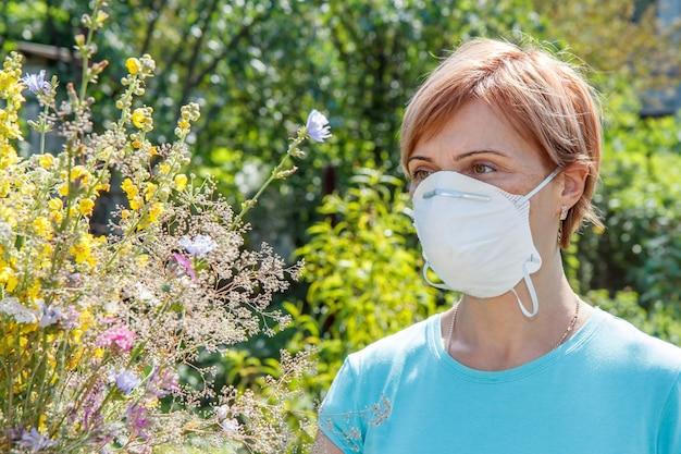 野花の花束を保持し、花粉に対するアレルギーと戦おうとしている保護マスクの女性。アレルゲンから鼻を守る女性。アレルギーの概念。