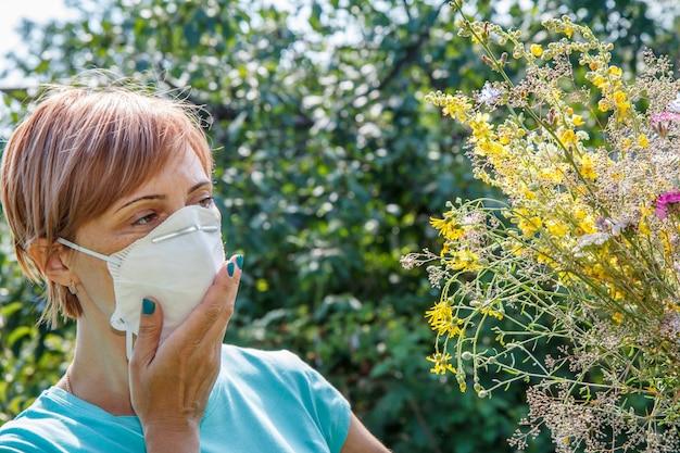 野花の花束を保持し、花粉に対するアレルギーと戦おうとしている保護マスクの女性。アレルゲンから鼻を守る女性