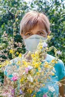 野花の花束を保持し、花粉に対するアレルギーと戦おうとしている保護マスクの女性。