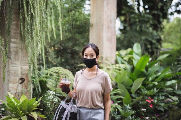アイスコーヒーを保持している防護マスクの女性