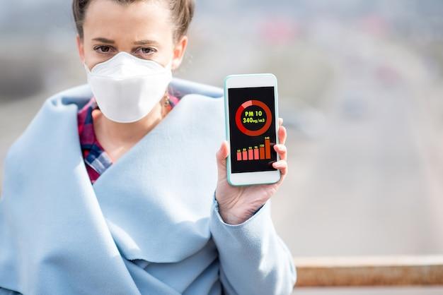 야외에서 pm10의 대기 오염 측정으로 스마트 폰을 들고 보호 마스크를 쓴 여성