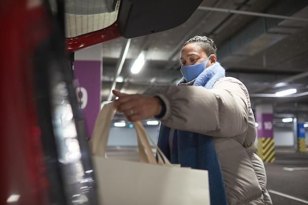 지하 주차장에 서있는 동안 그녀의 차에 쇼핑백을 포장하는 보호 마스크에 여자