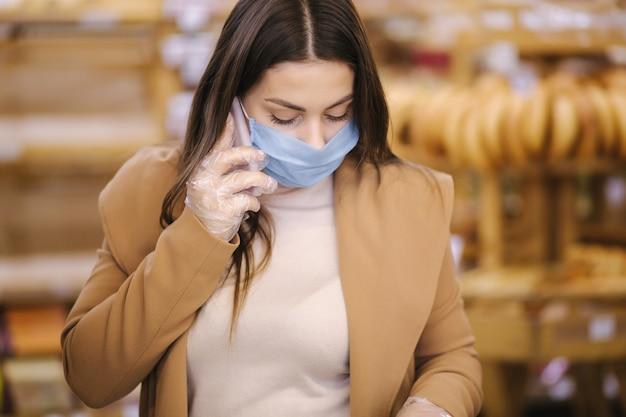 保護マスクの女性がスーパーマーケットで電話で話す