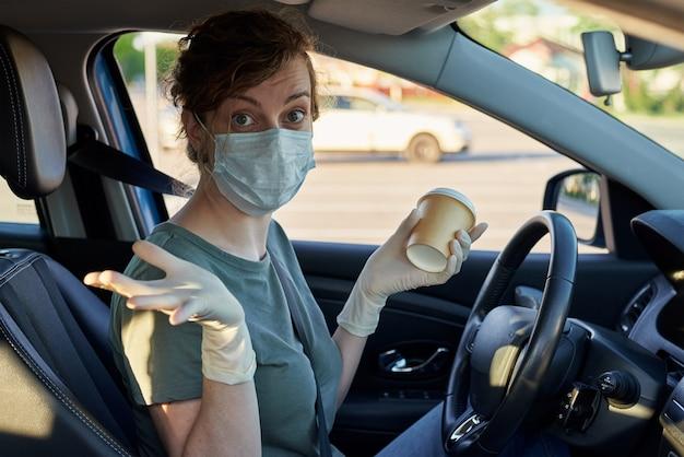 コーヒーを飲んで車を運転しようとしている保護マスクの女性。