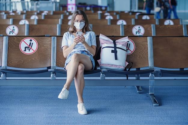空港で飛行機を待っている保護マスクの女性美しい女の子はで携帯電話を使用しています
