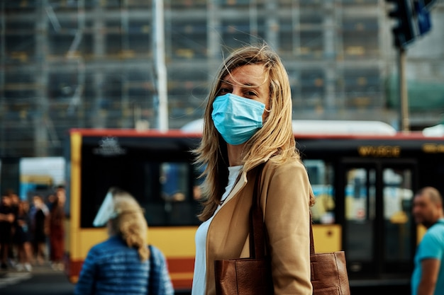 보호 마스크를 쓴 여성이 도시 거리를 걷다