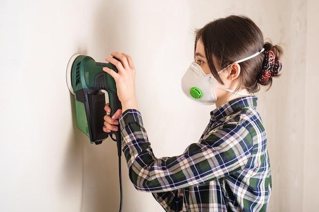 석고 벽 표면을 부드럽게하기 위해 전기 샌더로 작업하는 보호 마스크의 여성, 룸 리노베이션 개념