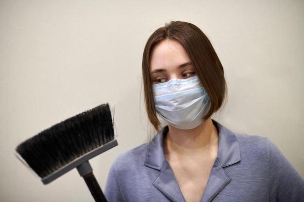 保護用医療マスクと青灰色の制服を着た女性は、長いハンドルで床のクリーニングブッシュを保持します