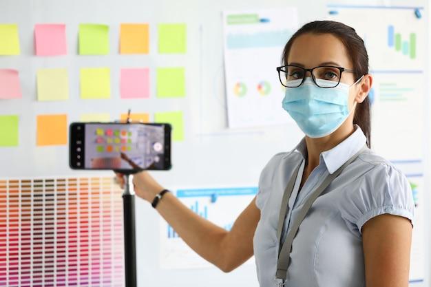 防護マスクの女性はビジネス会議を開催し、それをスマートフォンに記録します。