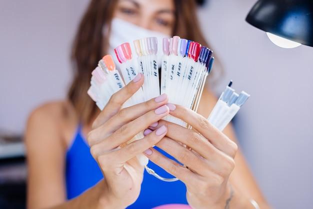 ビューティーサロンの保護用医療マスクの女性がパレットを保持し、色を選択しますマニキュア手順ネイルケアグランドオープン検疫が終了しました中小企業が再びオープンしました