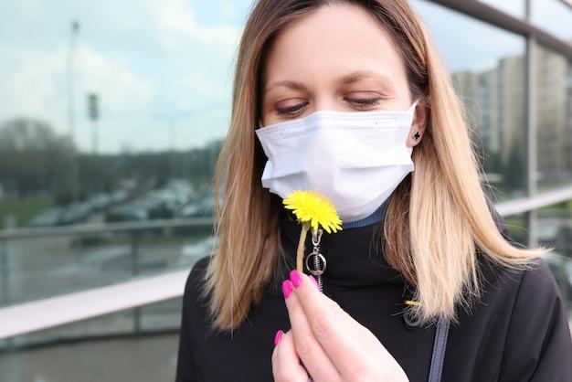 Женщина в защитной медицинской маске нюхает желтый цветок