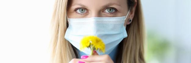 노란색 꽃을 킁킁 하는 보호 의료 마스크에 여자