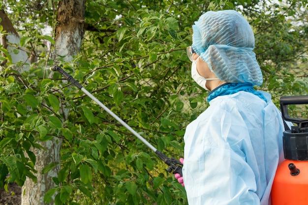 보호복과 마스크를 쓴 여성이 봄 과수원에서 곰팡이 질병이나 해충으로부터 사과 나무에 압력 분무기와 화학 물질을 뿌리고 있습니다.