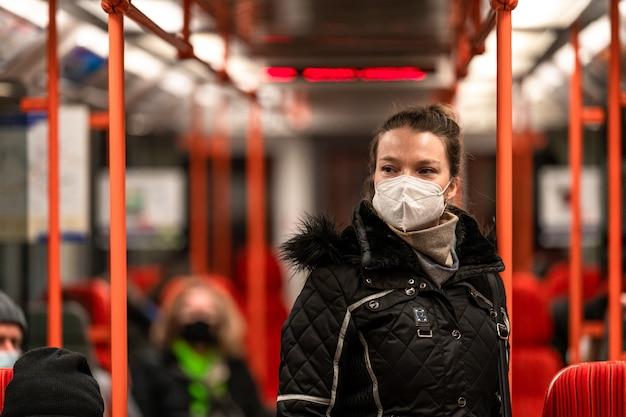 그녀의 얼굴에 인공 호흡기를 들고 대중 교통에있는 여성 코로나 바이러스 전염병