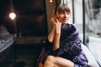 Woman in purple bathrobe in bedroom